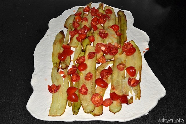 mettere al centro dell'impasto le fette di melanzane fritte ed i pomodori tagliati